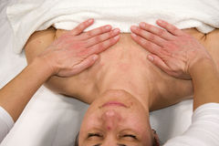 Thorax massage. A closeup of a natural mature woman having a massage at her thorax Stock Image