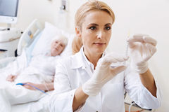Thorough qualified doctor estimating the dosage. Boosting immune system. Clever proficient young women measuring the contents of a syringe while preparing an Stock Photos