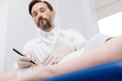 Thorough trained plastic surgeon marking problem spots Royalty Free Stock Photography
