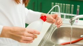 Thorough Washing. Young technician washing and rinsing thoroughly laboratory vessels Stock Photography
