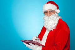 A thoroughly modern Santa claus checks his list. On clipboard. Isolated over blue background Royalty Free Stock Images