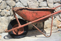 Thoroughly used up wheelbarrow - workaholic. Thoroughly used up wheelbarrow on a stony background - poor maintenace and/or workaholic treatment Royalty Free Stock Photos