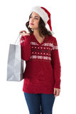 Thoughful brunette in santa hat holding shopping bag Stock Photos
