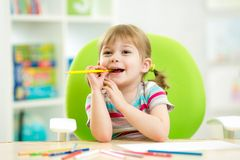 Thoughful child girl drawing with colourful. Thoughful child girl drawing with colorful pencils royalty free stock image