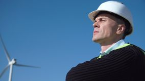 Thoughful engineer against wind turbine. Thoughful engineer with hard hat standing against wind turbine on sunny day stock video footage
