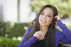 Thoughful Mixed Race Female Student with Pencil on Campus Stock Photo