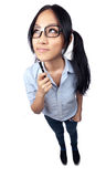 Thoughful Nerd Shot with a Wide Angle Lens. A wide angle full body shot of a nerdy Asian student holding a pen and looking up and away Stock Photography