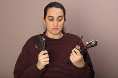Thoughful woman with tools. Thoughtful woman as she holds a spanner, a hammer and manifying glass in her hands in a DIY concept Royalty Free Stock Image