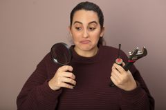 Thoughful woman with tools. Thoughtful woman as she holds a spanner, a hammer and manifying glass in her hands in a DIY concept Royalty Free Stock Images