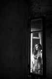 Thoughful young woman in pyjama and white panties standing near a window in her bedroom. Brunette girl in lingerie Royalty Free Stock Images