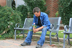 Thoughs of Love. Handsome man siitting on a park bench holding a pink rose Royalty Free Stock Photo