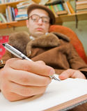 Thought. Young sitting man writes he's thought in the book Royalty Free Stock Image