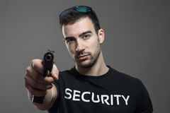 Thought security agent holding gun in one hand aiming at you. Royalty Free Stock Images