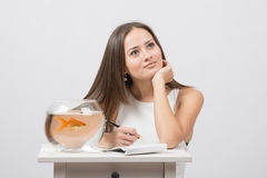 She thought about writing in a notebook desire to fulfill a goldfish Royalty Free Stock Images