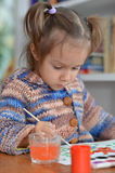 Thoughtful girl draws paint Royalty Free Stock Photography