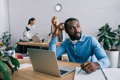 thoughtful african american businessman sitting at table and coworkers working behind in modern stock photo