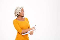 Thoughtful african american woman writing in notebook and thinking stock photography