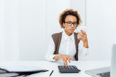 Thoughtful african woman accountant working with calculator and using smartphone Royalty Free Stock Photos