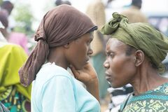 Thoughtful African women with scarf bounded hair accessories on street market in Uganda