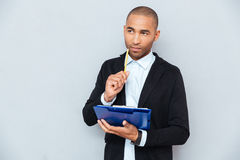 Thoughtful african young man writing on clipboard Stock Photos