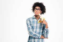 Thoughtful afro american man holding banana Stock Photography