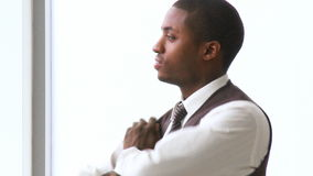 Thoughtful AfroAmerican businessman with folded arms in office