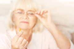 Thoughtful aging lady examining closely the pill at home. Taking care about myself. Attentive charming old lady sitting at home and holding the pill while stock photos