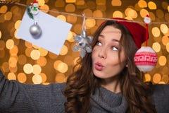 Thoughtful amusing female using handmade christmas decoration over glittering background Royalty Free Stock Photography