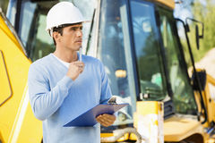 Thoughtful architect with clipboard and pen standing against earthmover at site Royalty Free Stock Image