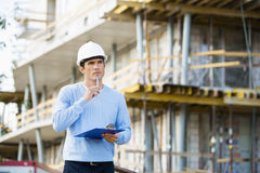 Thoughtful architect with clipboard and pen standing at site Royalty Free Stock Photos