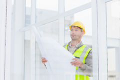 Thoughtful architect holding blueprint in office Royalty Free Stock Image