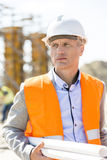 Thoughtful architect looking away while holding blueprints at construction site Stock Images