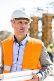 Thoughtful architect looking away while holding blueprints at construction site Royalty Free Stock Photos
