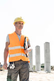 Thoughtful architect looking away while holding clipboard at construction site Stock Images