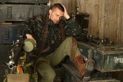 Thoughtful armed soldier sits Royalty Free Stock Image