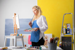 Thoughtful  artist looking at her painting Stock Images