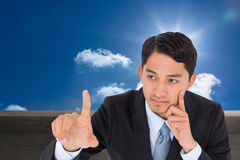 Thoughtful asian businessman pointing Stock Photo