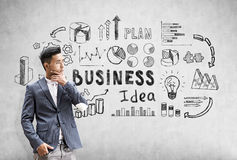 Thoughtful Asian businessman is standing near a concrete wall with black business idea sketch. Royalty Free Stock Photos