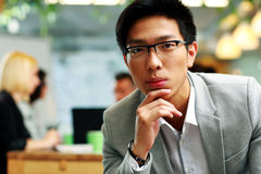Thoughtful asian man sitting in office Royalty Free Stock Photo