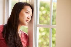 Thoughtful Asian Woman Looking Out Of Window Royalty Free Stock Image