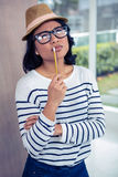 Thoughtful Asian woman with pencil on mouth Royalty Free Stock Photos