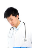 Thoughtful Asian young male doctor looking down Stock Photography