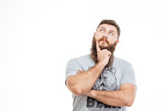 Thoughtful attractive bearded man looking up and thinking Stock Images