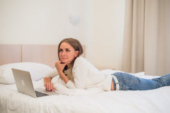 Thoughtful attractive blond woman using a laptop computer as she sits on the edge of a bed at home or in a hotel bedroom Stock Image
