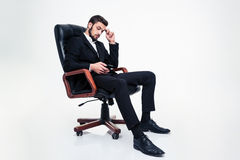 Thoughtful attractive businessmansitting in office chair and using mobile phone. Full length of thoughtful attractive bearded businessman in black suit and shoes Royalty Free Stock Photos
