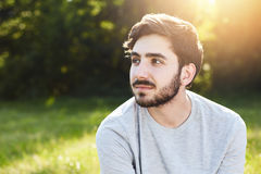 Thoughtful attractive male with dark mustache and beard looking aside into distance dreaming about something pleasant while relaxi Royalty Free Stock Photography