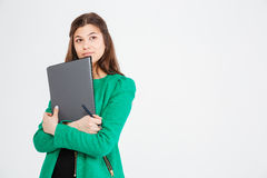 Thoughtful attractive woman in green jacket holding folders and thinking Royalty Free Stock Photo