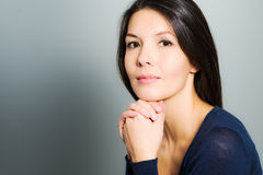 Thoughtful attractive woman with a serene face. And enigmatic smile standing with her hand to her chin looking pensively at the camera Stock Photo