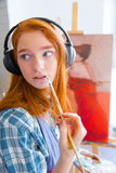 Thoughtful attractive young female painter listening to music and painting Stock Images