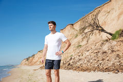 Thoughtful attractive young man standing on the beach and thinking Royalty Free Stock Photo